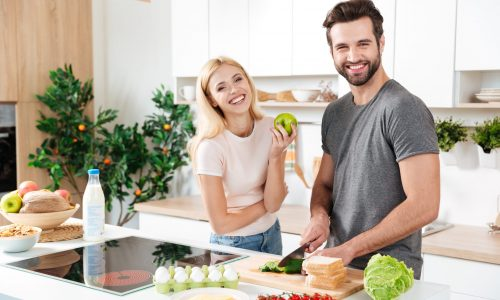 Smiling couple spending time together in the kitchen at home